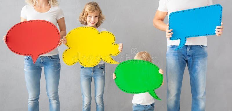 Lycklig familj som rymmer det färgrika pappers- anförandebubblamellanrumet arkivbilder
