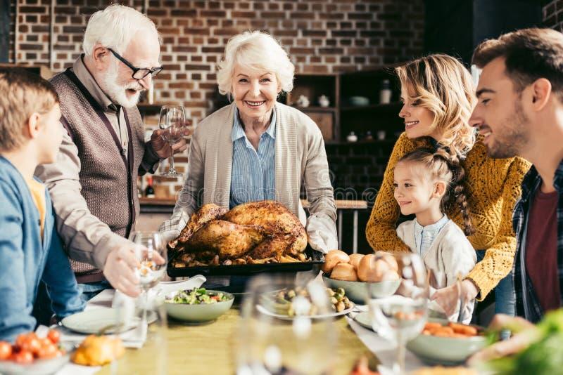 lycklig familj som ser den läckra tacksägelsekalkon i händer arkivbild