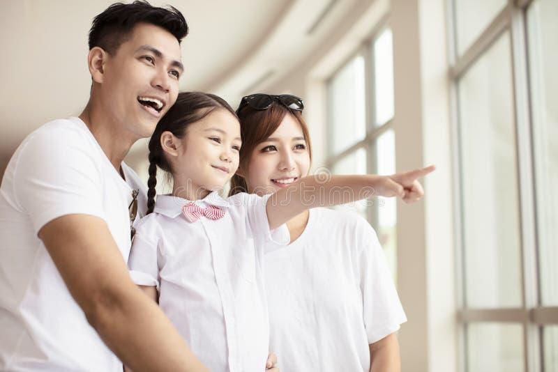 Lycklig familj som ser till och med fönstret royaltyfri foto