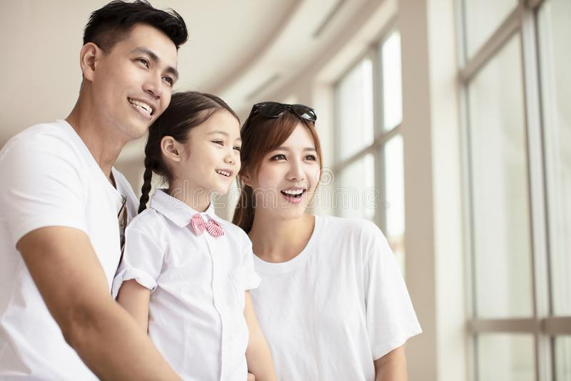 Lycklig familj som ser till och med fönstret arkivfoto