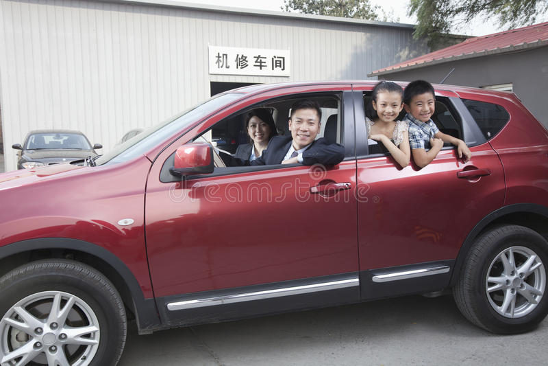 Lycklig familj som ser ut ur en bil arkivbild