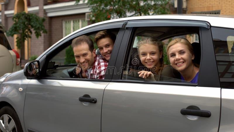 Lycklig familj som sitter i bil och ler in i kameran, bilköpandeservice royaltyfri fotografi