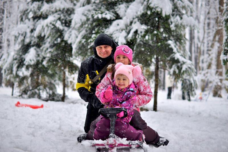 Lycklig familj som sitter på en släde i vintern fotografering för bildbyråer
