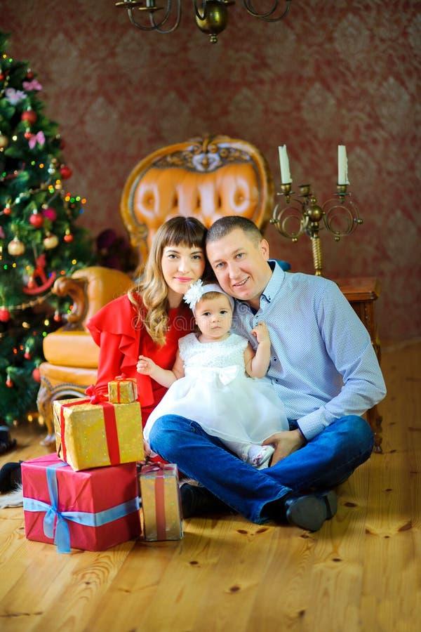 Lycklig familj som sitter på golvet nära askar med gåvor och att le arkivfoton