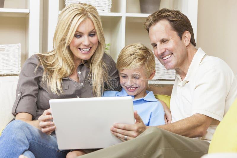 Lycklig familj som sitter på sofaen genom att använda bärbar datordatoren arkivbild