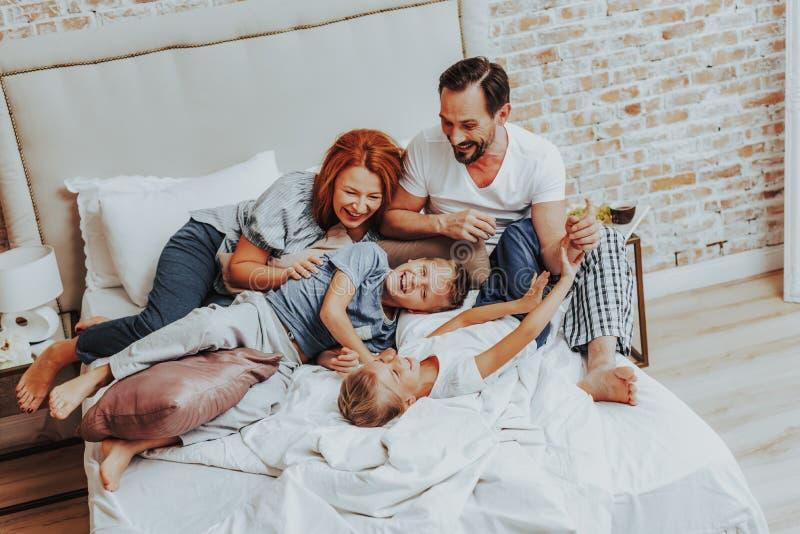 Lycklig familj som skrattar, medan spela tillsammans i säng fotografering för bildbyråer