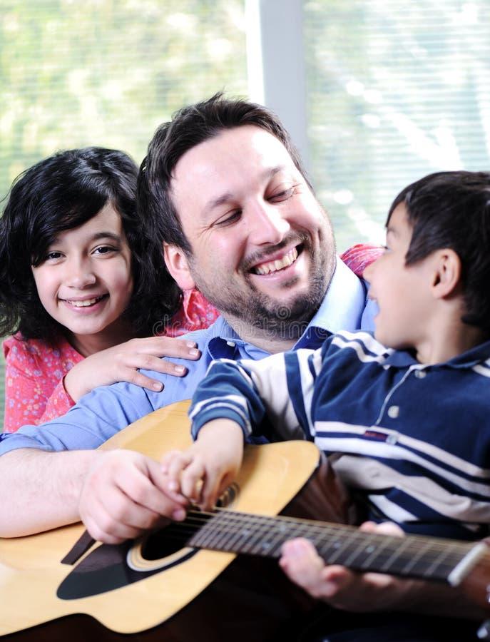 Lycklig familj som spelar gitarren royaltyfri foto