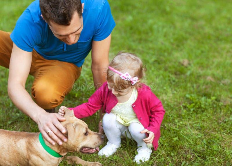 Lycklig familj som spelar i parkera med hans hund fotografering för bildbyråer