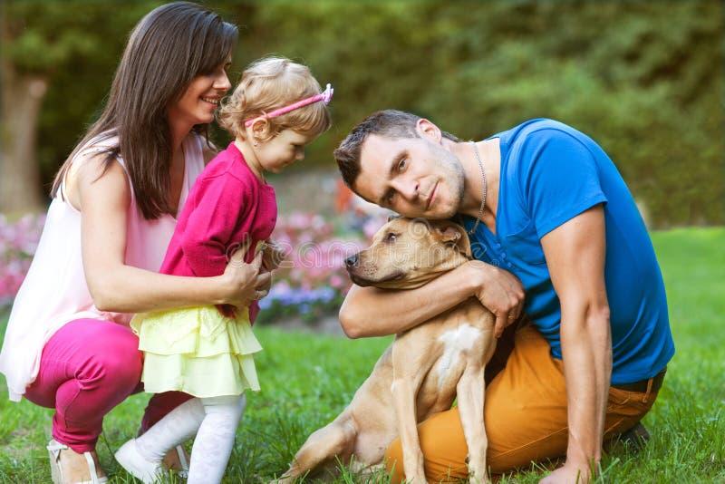 Lycklig familj som spelar i parkera med hans hund royaltyfri fotografi