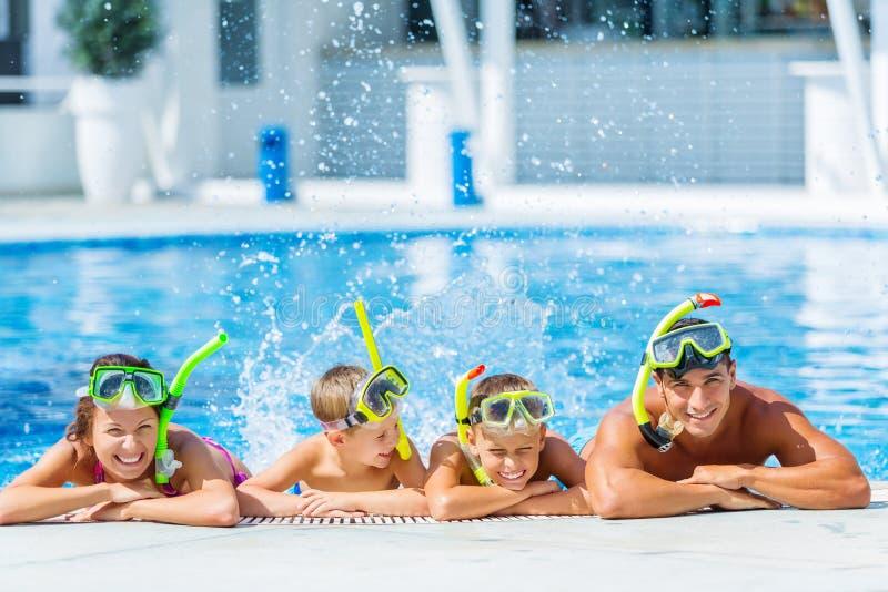 Lycklig familj som spelar i simbassäng Sommar royaltyfri foto