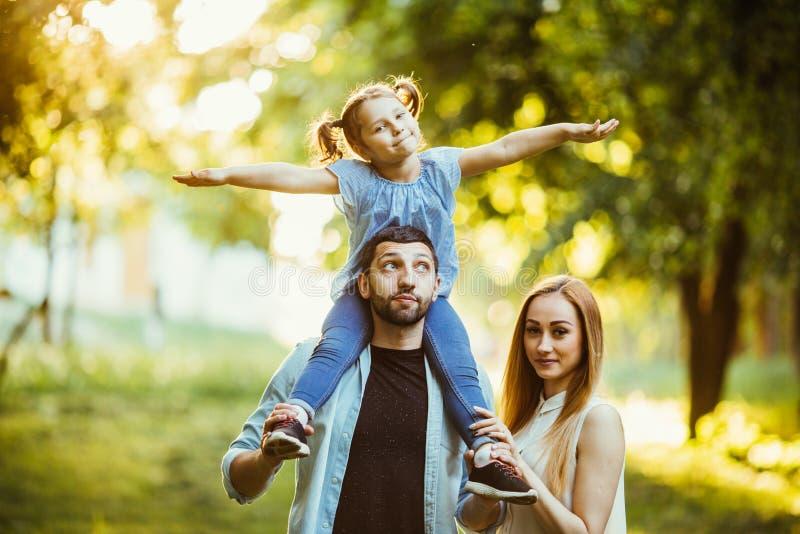 Lycklig familj som spelar i solljus för sen eftermiddag för natur i nedgången, sommar Moder, fader och dotter som spelar på gräse arkivfoton