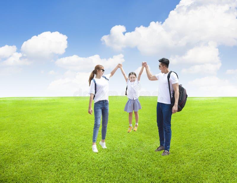 Lycklig familj som spelar med barnet i parkera arkivfoto