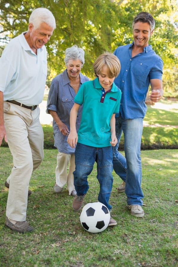 Lycklig familj som spelar på bollen royaltyfria bilder