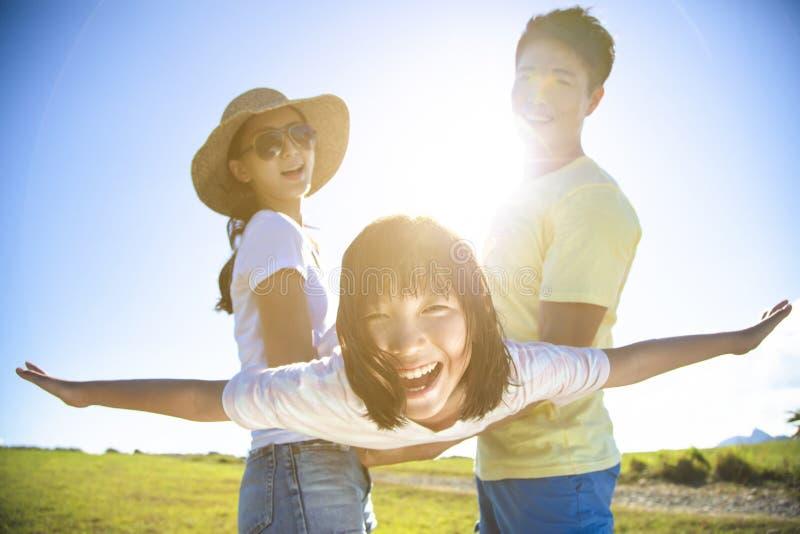 Lycklig familj som spelar på gräset fotografering för bildbyråer