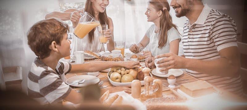 Lycklig familj som till varandra talar, medan ha frukosten tillsammans arkivbild