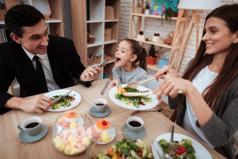 Lycklig familj som tillsammans äter disk på tabellen Föräldrar med deras dotter som samlas på tabellen royaltyfria bilder