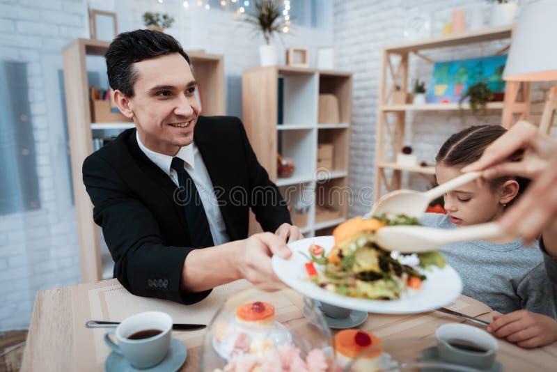 Lycklig familj som tillsammans äter disk på tabellen Föräldrar med deras dotter som samlas på tabellen royaltyfri bild