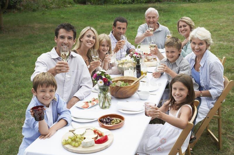 Lycklig familj som tillsammans äter middag i trädgård royaltyfri foto