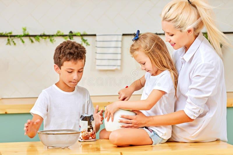Lycklig familj som tillsammans förbereder bakelse i kök arkivfoto