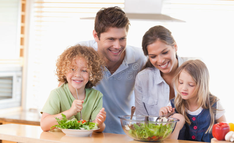 Lycklig familj som tillsammans förbereder en sallad arkivbilder