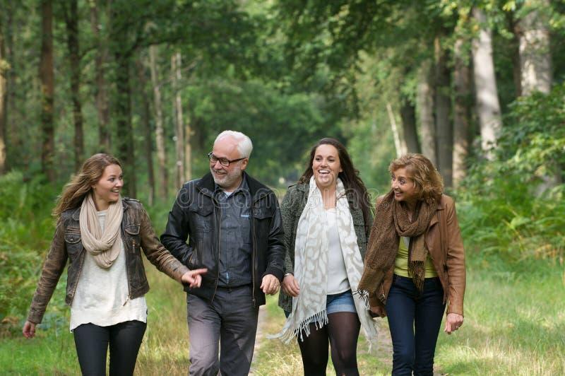 Lycklig familj som tillsammans går i skogen arkivfoton