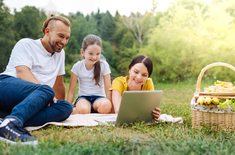 Lycklig familj som tillsammans håller ögonen på en film på picknick arkivfoto