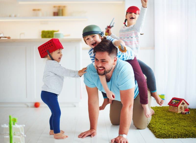 Lycklig familj som tillsammans hemma spelar och att rida på fader arkivfoton