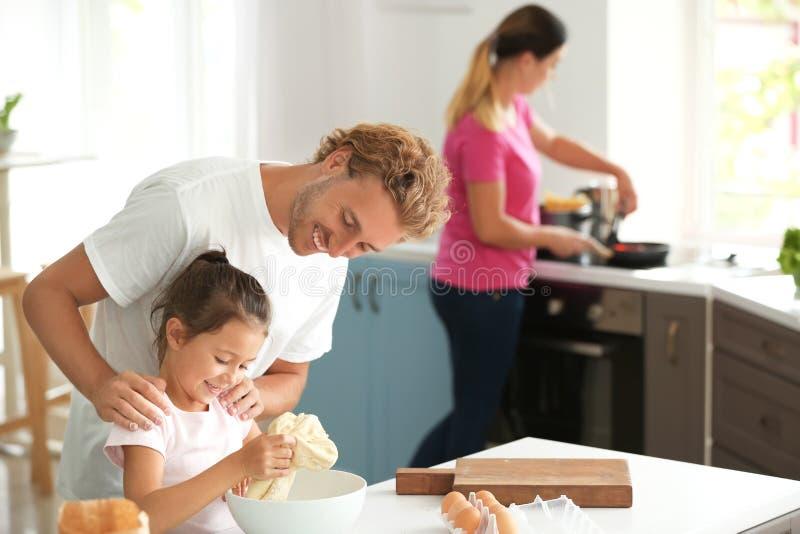 Lycklig familj som tillsammans lagar mat i k?k royaltyfri fotografi