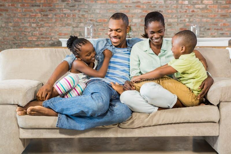 Lycklig familj som tillsammans poserar på soffan arkivfoto