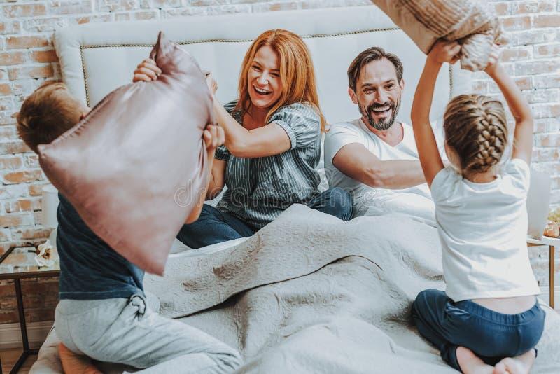 Lycklig familj som tillsammans slåss vid kudden i säng arkivbild