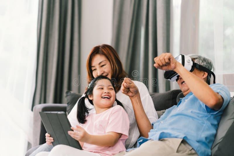 Lycklig familj som tillsammans spelar virtuell verklighetleken, flicka för ung unge som använder den digitala minnestavlan, farfa arkivfoto