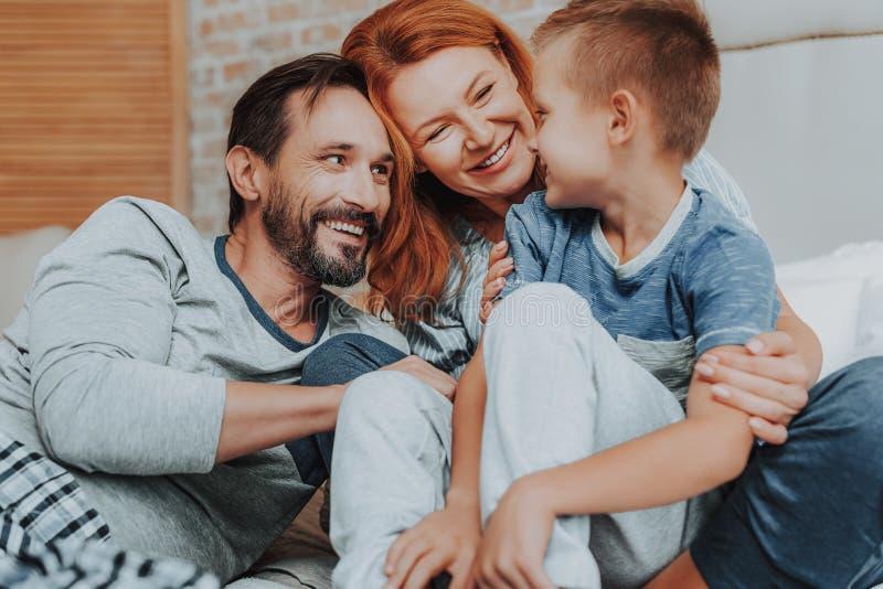 Lycklig familj som tillsammans spenderar tid hemma arkivbild