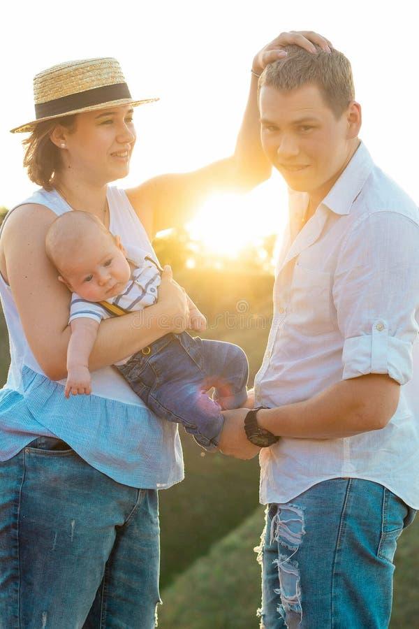 Lycklig familj som tillsammans spenderar tid på solnedgången arkivbilder