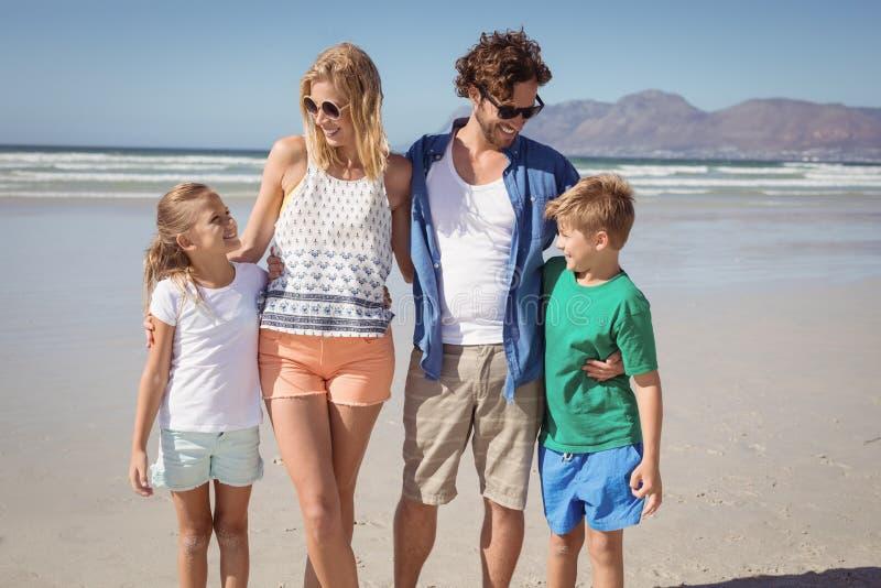 Lycklig familj som tillsammans står på stranden arkivbilder