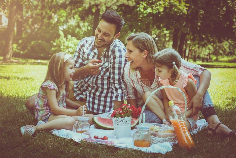 Lycklig familj som tillsammans tycker om i picknick royaltyfri foto