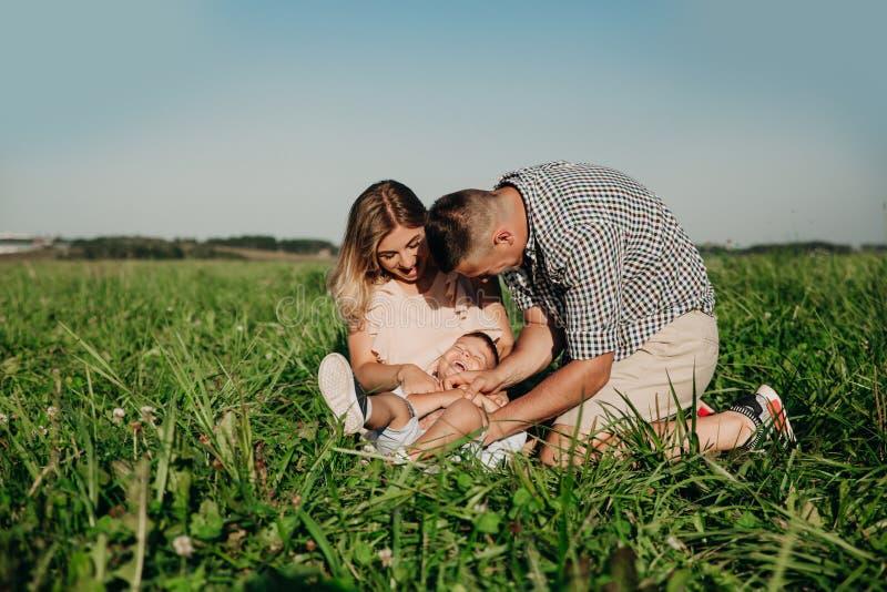 Lycklig familj som tillsammans tycker om i sommardag Familj som sitter på gräs och har gyckel fotografering för bildbyråer