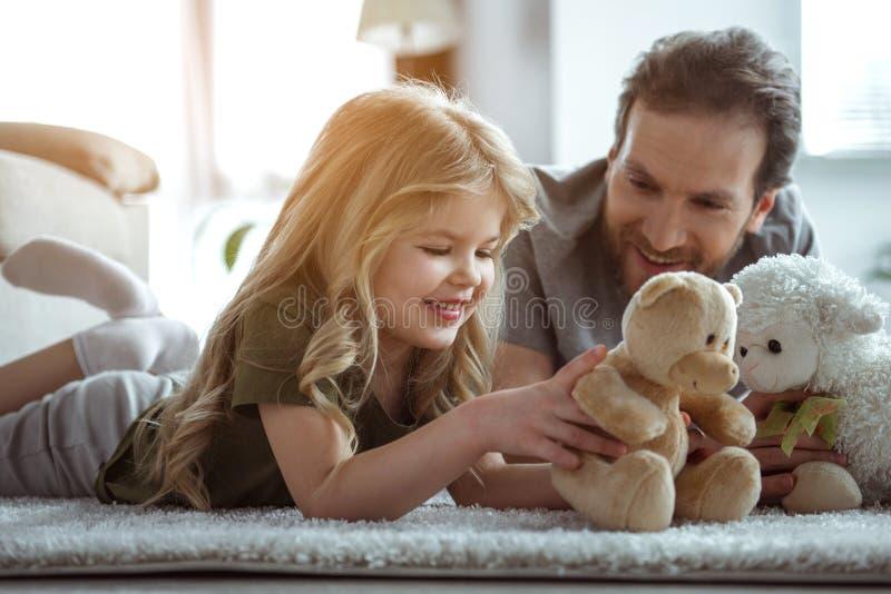 Lycklig familj som tillsammans underhåller med leksaker i hem royaltyfria bilder