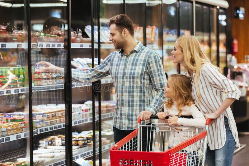 Lycklig familj som tillsammans väljer livsmedel royaltyfri foto