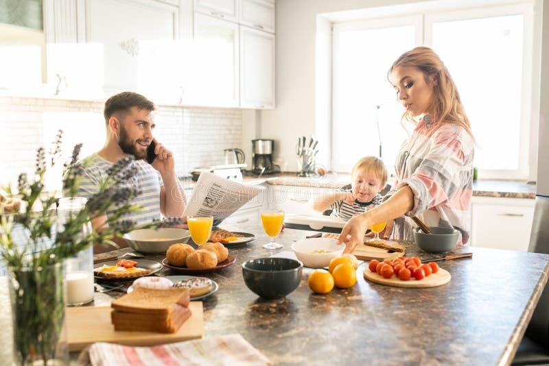 Lycklig familj som tycker om frukosten i morgon arkivfoton