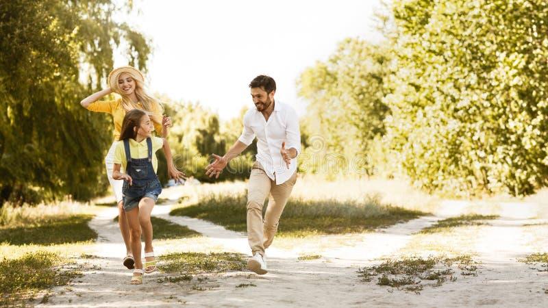 Lycklig familj som tycker om helger och spring på banan arkivbild