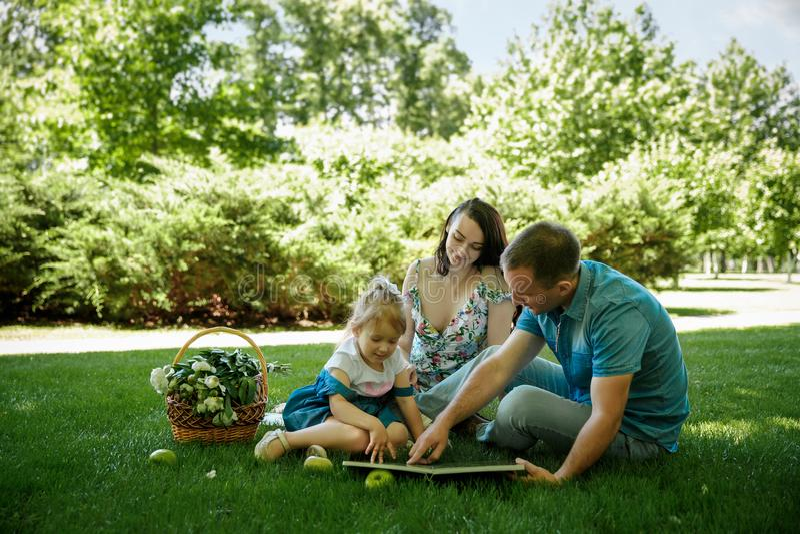 Lycklig familj som tycker om picknicken i natur arkivbild