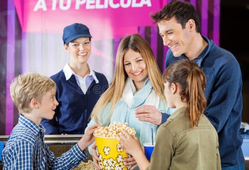 Lycklig familj som tycker om popcorn på biomedgivandet arkivbild
