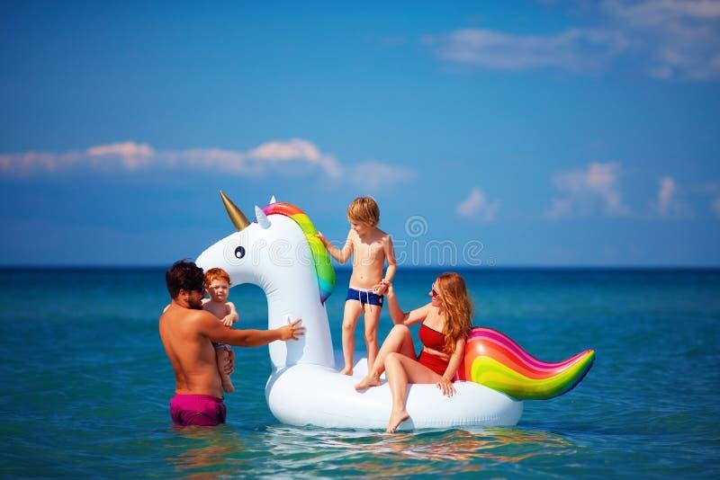 Lycklig familj som tycker om sommarsemester och att ha gyckel i vatten på uppblåsbar enhörning arkivfoto