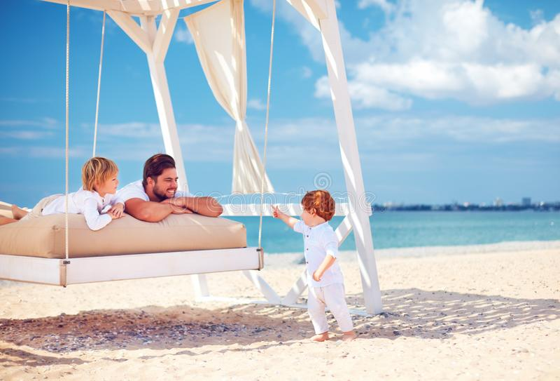 Lycklig familj som tycker om sommarsemester på havsstranden arkivfoto
