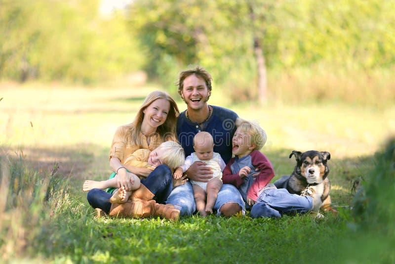 Lycklig familj som utanför skrattar samman med hund royaltyfria foton