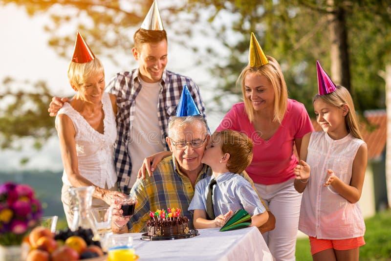 Lycklig familj som utomhus firar födelsedag arkivfoto