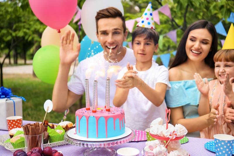 Lycklig familj som utomhus firar födelsedag på tabellen med kakan royaltyfri fotografi