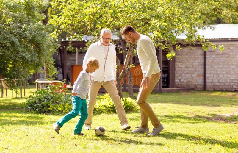 Lycklig familj som utomhus spelar fotboll arkivfoton