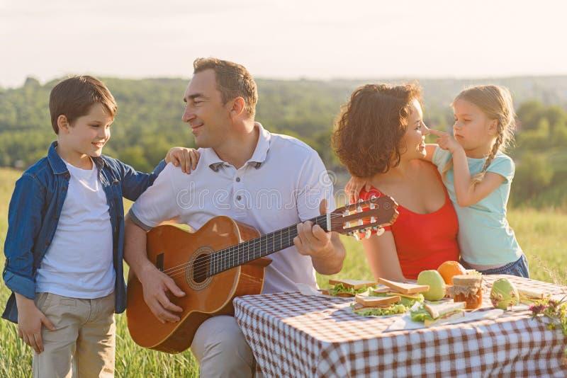 Lycklig familj som utomhus tycker om lunch fotografering för bildbyråer