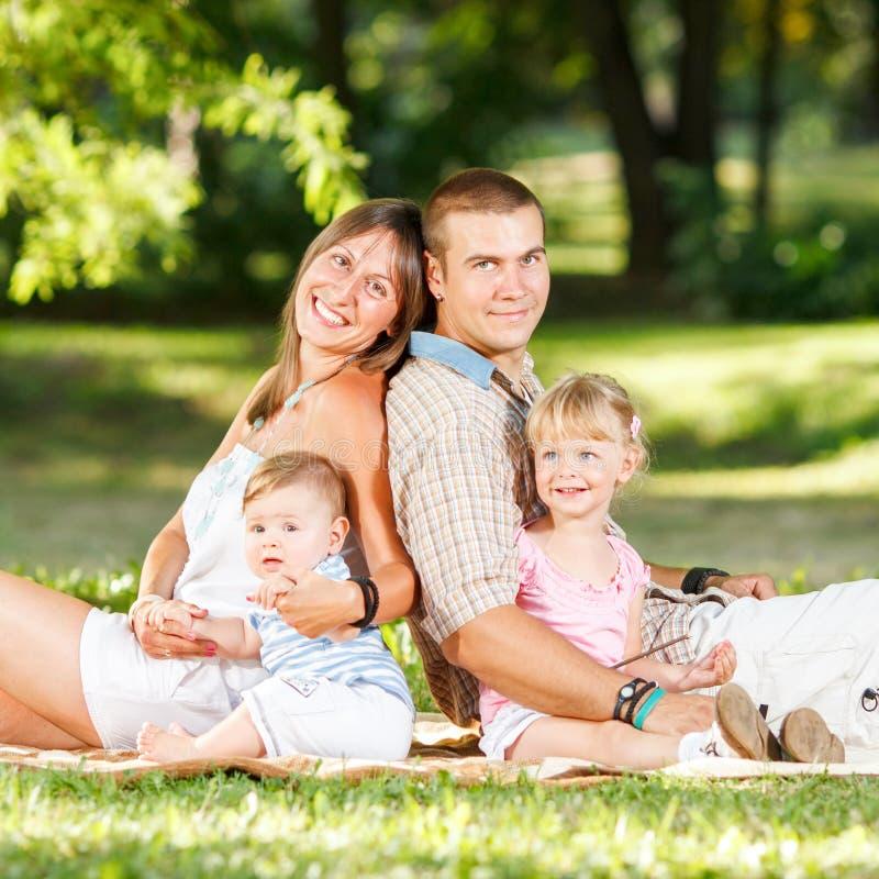 Lycklig familj som vilar i parkera royaltyfria bilder